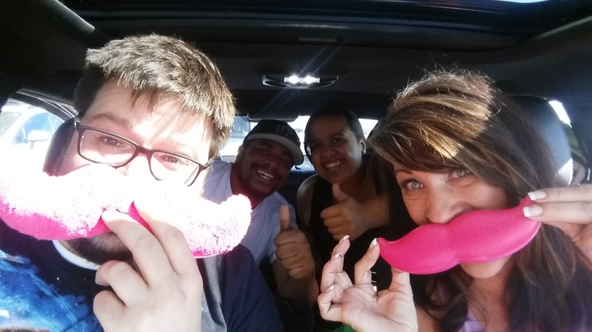 Deanna and I modeling the two Lyft mustaches in her car, as Richard and Sophia can't help but smile.